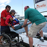 Skipper Sarah Everhart Skeels, Tiverton, RI, is helped into the boat by Mike Pinckney and Brian Todd  before sailing with Cindy Walker, Middletown, RI, the only all female team competing in The Skud 18 class, during the C. Thomas Clagett, Jr. Memorial Clinic & Regatta at Newport, Rhode Island hosted by Sail Newport at Fort Adams. <br /> The Clagett is North America's premier event for sailors with disabilities with sailors competing in the 3 Paralympic class boats and is an integral part of preparation for athletes preparing for  Paralympic and world championship racing. Newport, Rhode Island, USA. 26th June 2015. Photo Tim Clayton