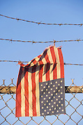 American flag caught on barbed wire at top of fence.