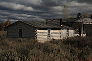 Storm clouds threaten as the lowering sun illuminates a historic cabin in Grand Tetons National Park.