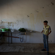 A young syrian refugee stands in a improvised kitchen at Wadi Khaled's refugee center for Syrian families.