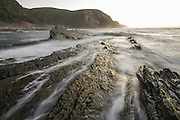 Gentle waves breaking over coastal rocks at dawn over the Tsitsikamma Marine Protected Area; Garden Route National Park; Western Cape; South Africa
