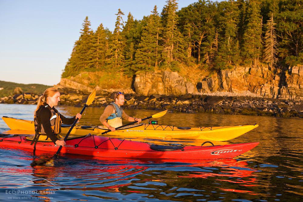 A man and woman sea kayaking near Sheep Porcupine Island in Maine's Acadia National Park.  Bar Harbor.
