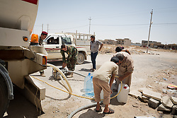 © Licensed to London News Pictures. Hamdaniyah, Iraq. 26/07/2014. Iraqi Christian refugees from Mosul fill water containers from a tanker provided by Kurdish Zeravani soldiers in Hamdaniyah, Iraq.<br /> <br /> Having taken over Mosul Iraq's second largest city in June 2014, fighter of the Islamic State (formerly known as ISIS) have systematically expelled the cities Christian population. Despite having been present in the city for more than 1600 years, Christians in the city were given just days to either convert to Islam, pay a tax for being Christian or leave; many of those that left were also robbed at gunpoint as they passed through Islamic State checkpoints.. Photo credit : Matt Cetti-Roberts/LNP