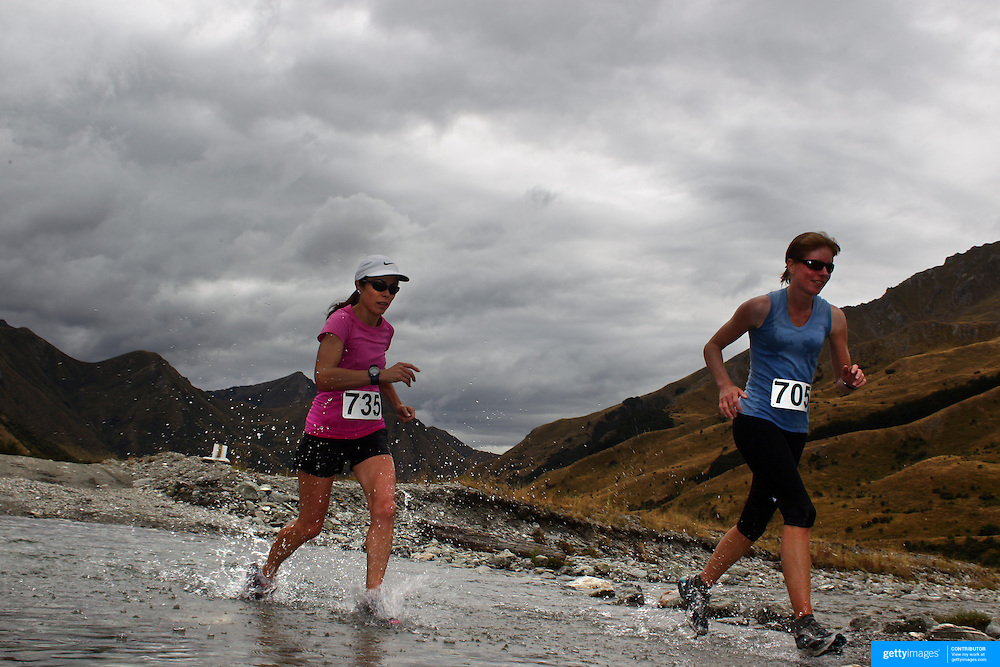 Runners Nicola Greer (left) and Robyn Clements cross Moke Creek on the Ben Lomond High Country Station during the Pure South Shotover Moonlight Mountain Marathon and trail runs. Moke Lake, Queenstown, New Zealand. 4th February 2012. Photo Tim Clayton