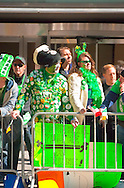 "MARCH 17, 2011 - MANHATTAN: Crowds at St. Patrick's Day Parade, man covered with Irish pins, face painted green, white, and orange, and with neon green sign saying, ""Blomberg You're a Drunk!"" on Fifth Avenue by E 51 St, New York City, NY, USA."