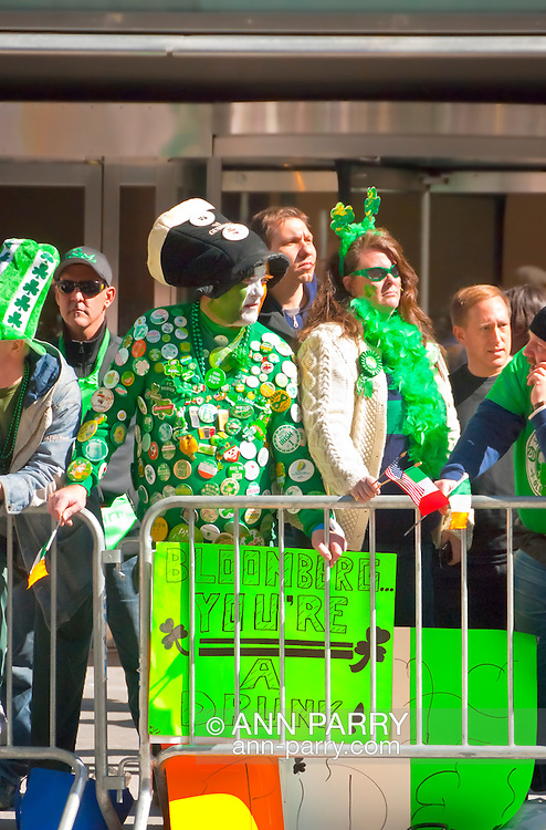 """MARCH 17, 2011 - MANHATTAN: Crowds at St. Patrick's Day Parade, man covered with Irish pins, face painted green, white, and orange, and with neon green sign saying, """"Blomberg You're a Drunk!"""" on Fifth Avenue by E 51 St, New York City, NY, USA."""
