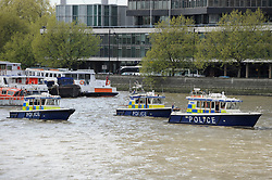 © Licensed to London News Pictures. 10/04/2017. London, UK. Police boats patrol the River Thames as mourners pay their respects as the hearse carrying the coffin of PC Keith Palmer passes by on Lambeth Bridge.  PC Palmer was killed in last month's attack in Westminster.  5,000 police officers have lined the funeral route from Westminster Abbey to Southwark Cathedral.   Photo credit : Stephen Chung/LNP