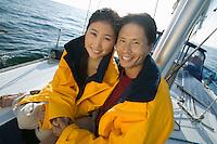 Couple wearing yellow anoraks on yacht (portrait)
