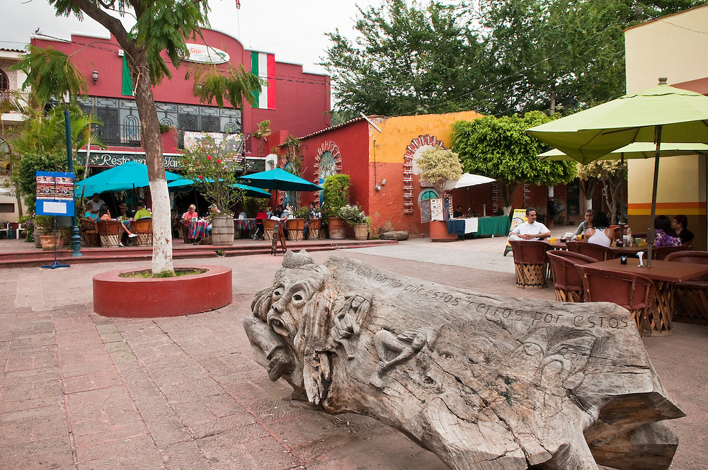 Wooden sculpture and cafes on the main plaza in Ajijic, Lake Chapala, Jalisco, Mexico.
