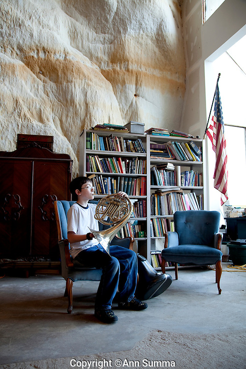 """Festus, Missouri: Perry Sleeper practices French horn after school in the """"living room"""" of his 2,000 square foot home. It is built inside a 17,000 square foot cave in this small town south of St. Louis."""