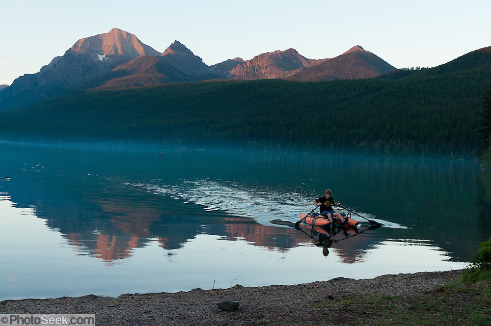 A man paddles a pontoon boat in Bowman Lake as sunset illuminates the Rocky Mountains in Glacier National Park, Montana, USA.