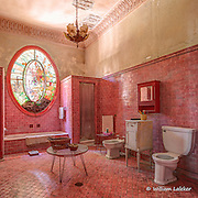 A large pink bathroom of a mansion built in 1926.
