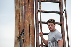 good looking man holding on to a rooftop ladder