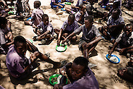Schoolchildren getting schoolfood from a donation. The youngest first. They get salza and greens with tomato.