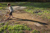 "So, what is it you like about mud?  ""Ahh...pretty much everything.""  -Five year old Ryley Macleod plays in a puddle adjacent to his house on Maggie Street in Calistoga."