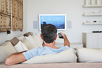 Man watching television sitting on sofa in living room back view