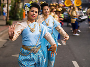 30 OCTOBER 2014 - BANGKOK, THAILAND:  Traditional dancers on Chakkaphatdi Phong Street during the parade marking the start of the annual temple fair at Wat Saket. Wat Saket is on a man-made hill in the historic section of Bangkok. The temple has golden spire that is 260 feet high which was the highest point in Bangkok for more than 100 years. The temple construction began in the 1800s in the reign of King Rama III and was completed in the reign of King Rama IV. The annual temple fair is held on the 12th lunar month, for nine days around the November full moon. During the fair a red cloth (reminiscent of a monk's robe) is placed around the Golden Mount while the temple grounds hosts Thai traditional theatre, food stalls and traditional shows.  PHOTO BY JACK KURTZ
