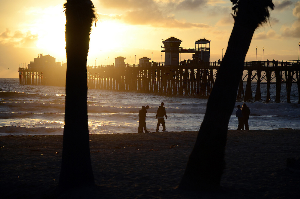 Silhouette of trees and men walking on beach near Oceanside Pier at sunset. Oceanside, CA. USA