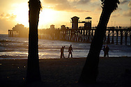 Silhouette of trees and men walking on beach near Oceanside Pier at sunset. Oceanside, CA. USA