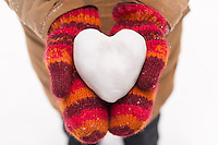 Woman in red mittens holding a heart made of snow, closeup of hands, romantic concept