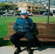 Old man sitting on a park bench, USA