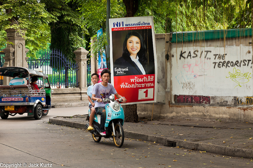 03 JULY 2011 - BANGKOK, THAILAND:   A tuk-tuk (three wheeled taxi) and motor scooter drive past a Yingluck Shinawatra poster on election day in Bangkok, Thailand, Sunday July 3. She is running for Prime Minister of Thailand, the graffiti on the wall refers to Thai Foreign Minister Kasit Piromya, a Yellow Shirt leader who endorsed a violent crackdown against the Red Shirts in 2010. The Red Shirts are the street movement of Pheu Thai, the party of Yingluck Shinawatra. More than 47,000,000 Thais were registered to vote in Sunday's election, which had turned into a referendum on the current government, led, by the Thai Democrats and the oppositionPheu Thai party. Pheu Thai is the latest political incarnation of ousted Thai Prime Minister Thaksin Shinawatra. PT is led by his youngest sister, Yingluck Shinawatra, who is the party's candidate for Prime Minister. Exit polling by three Thai polling firms showed Pheu Thai winning a landslide election.   PHOTO BY JACK KURTZ