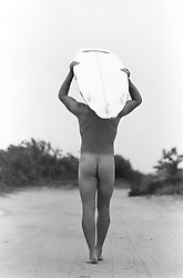 Naked man walking away carrying his surfboard on his head