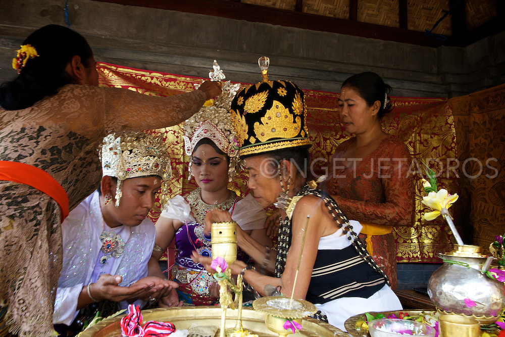 Balinese Wedding Ceremony .<br /> <br /> The main part of this wedding ceremony is held in the groom's house, to welcome the bride to become a part of the groom's family.<br /> There are several parts in this Ceremony, which is called Sudi Widani.<br /> Because the bride has a different religion and becomes Hindhu this is the ceremony for the bride and is witnessed by the Local Leader in the village, a Holy man and by family of the bride and family of the groom.<br /> <br /> After the bride has been through this Ceremony than there is the next Ceremony, which is the Mekala-Kalaan,<br /> which is the bride's and groom's top ceremony.<br /> <br /> In this Ceremony they both have to do a few steps and will be guided by the priest and witnessed by the family and which is followed by praying in the temple in the house.<br /> This is Final step of the Wedding Ceremony for Hindhus in Bali.<br /> <br /> After these Ceremonies their is a  Receiption in the groome's house for family and relatives and some close friends who witnessed the marriage.<br /> <br /> KlungKung, Bali<br /> 24 December 2012<br /> &copy;Ingetje Tadros