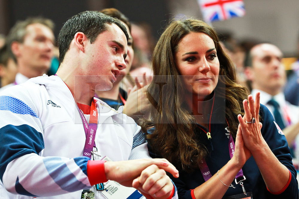 © Licensed to London News Pictures. 05/08/2012. London,UK. Catherine, Duchess of Cambridge (R) applauds from the stand next to British gymnast Kristian Thomas (L) during the London 2012 Olympic Games Artistic Gymnastics competition.  Photo credit : Bogdan Maran/LNP/BPA