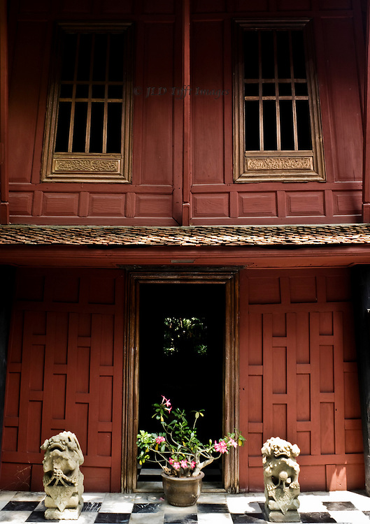 One doorway to the Jim Thompson house in Bangkok.  Potted plant centered in the doorway (visitors are not supposed to use it) flanked by two ancient dragon sculptures.  The house walls are red-toned wooden panels in traditional Thai style.