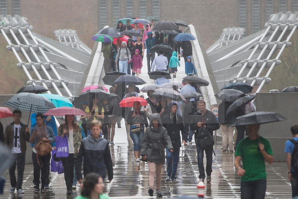 © licensed to London News Pictures. London, UK 30/07/2013. People walking across the Millennium Bridge under the rain in central London on Tuesday, July 30, 2013. Photo credit: Tolga Akmen/LNP
