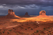 The warm tone of a desert sun set partially lights Monument Valley after a late summer rain storm. Photo by Colin E Braley (Wild West-Media)