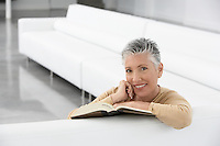Woman with book on sofa smiling portrait