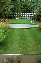 Three 'floating' steel trays creating different levels of lawn. Workshop in distance clad with aluminium reflective disks. Design Diarmuid Gavin