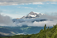 Clouds part in Thompson Pass to reveal Hogback Glacier and the Lowe River Valley near Valdez in Southcentral Alaska. Summer. Morning.