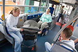 Woman sitting on bus in designated area for wheelchair users interacting with baby in pushchair,