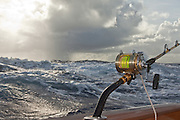 Single bent but outfit in teak coverering board with stormy seas and sky behind.