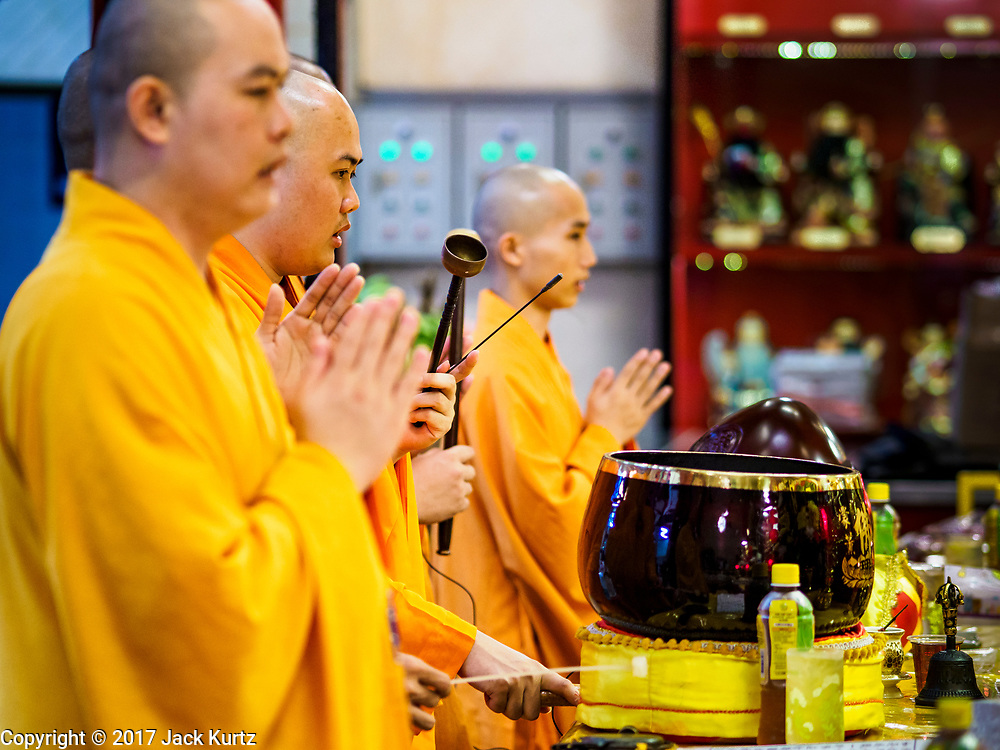 """22 AUGUST 2017 - BANGKOK, THAILAND: Mahayana Buddhist monks lead a ceremony on the first day of Hungry Ghost Month at the Poh Teck Tung Shrine in Bangkok's Chinatown. The seventh lunar month (August - September) is when many Chinese believe Hell's gate will open to allow spirits to roam freely in the human world. Many households and temples hold prayer ceremonies throughout the month-long Hungry Ghost Festival (Phor Thor) to appease the spirits. During the festival, believers will also worship the Tai Su Yeah (King of Hades) in the form of paper effigies which will be """"sent back"""" to hell after the effigies are burnt.      PHOTO BY JACK KURTZ"""