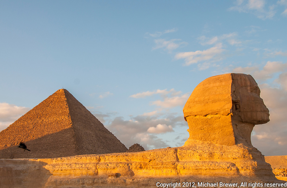 The sun shining off the Sphinx and the Great Pyramid near sunset at Giza, Egypt.