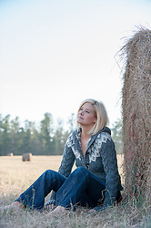 blonde girl outdoors by hay bales