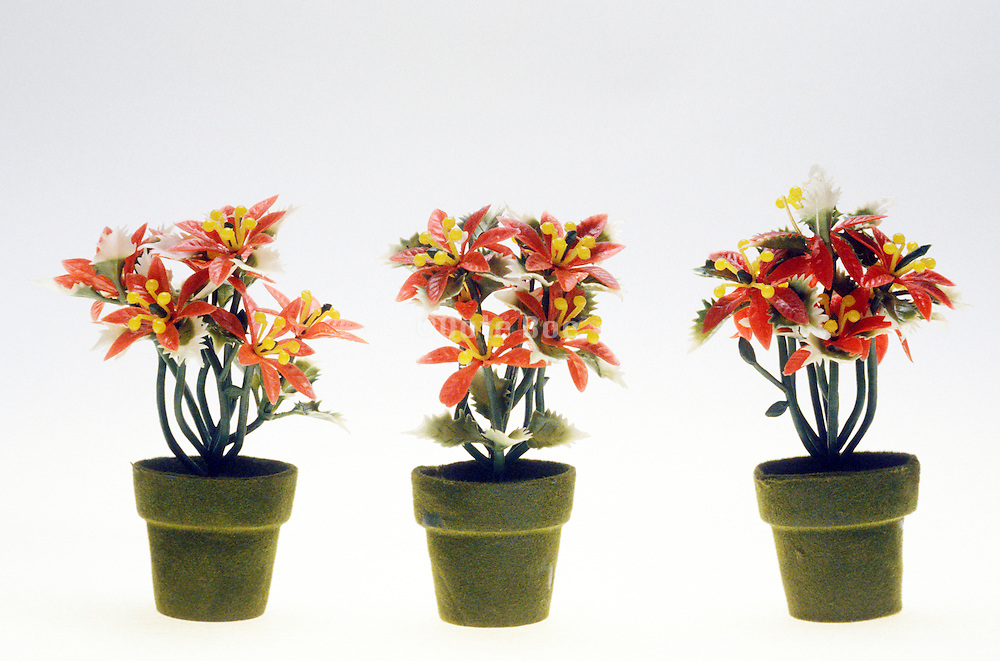Still life of three plastic plants in flower pots