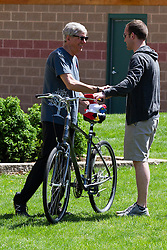 10 May 2014:  Normal Mayor Chris Koos presents a bicycle to the photo winner contest Matt Schienberg of Normal 25th anniversary celebration of the Constitution Trail ceremony at Connie Link Amphitheater in Normal Illinois