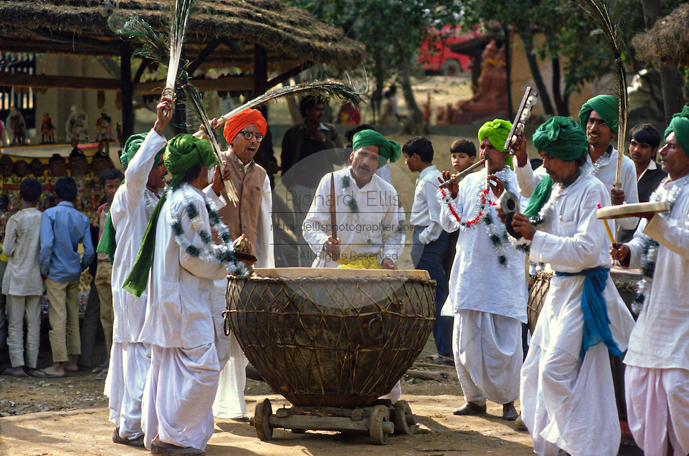 Turbaned Indian men play traditional drums and musical instruments during the Surajkund mela in Haryana, India.