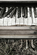 I found this homeless piano outside at a small country truck stop, sitting in a remote and muddy dirt corner at the end of a line of parked trucks. It was very weathered and broken up from being outside through Arizona heat and Montana cold year after year, and stood as the centerpiece of a small junk pile of assorted debris and common trash. It was probably abandoned there on a midnight dump-and-run mission, and not left for live music at back lot trucker parties.<br />
