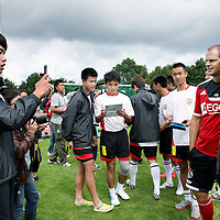 Nederland, Amsterdam , 30 juli 2013.<br /> Project met Chinese voetballers die een traineeship bij Ajax kunnen verdienen.<br /> Op de foto: Chinese voetballers met oud International Ronald de Boer op de foto.<br /> Project with Chinese football players who can earn a traineeship at Ajax. Taking pictures and posing with former international top player Ronald de Boer.