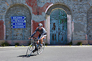 Cyclist riding British Scott bike passes signpost on The Stelvio Pass, Passo dello Stelvio, Stilfser Joch, in Northern Italy