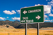 A road sign near Eagle Nest, New Mexico with arrows pointing the way towards Cimarron, Taos, and Texas for travelers coming from Red River.