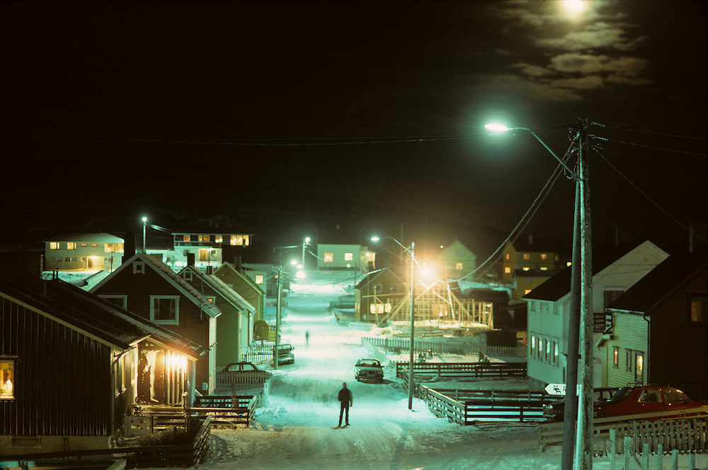 Norway, Moon rises above village streets in the arctic town of Bugoynes in arctic Norway in early November