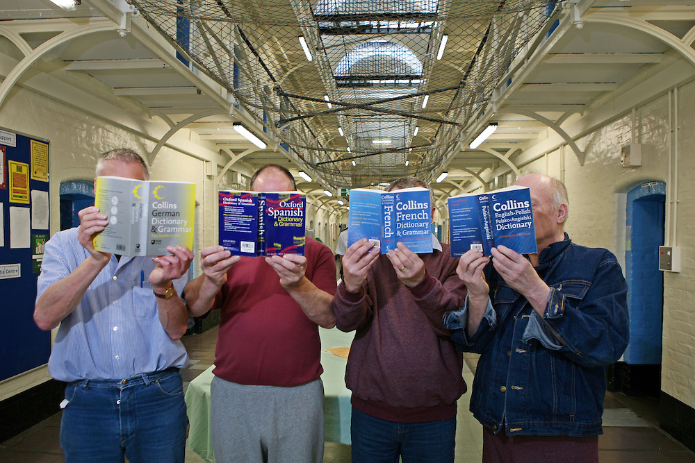 Prisoners on the Vulnerable Prisoner Unit hold up translation dictionaries in different languages. HMP Wandsworth, London, United Kingdom