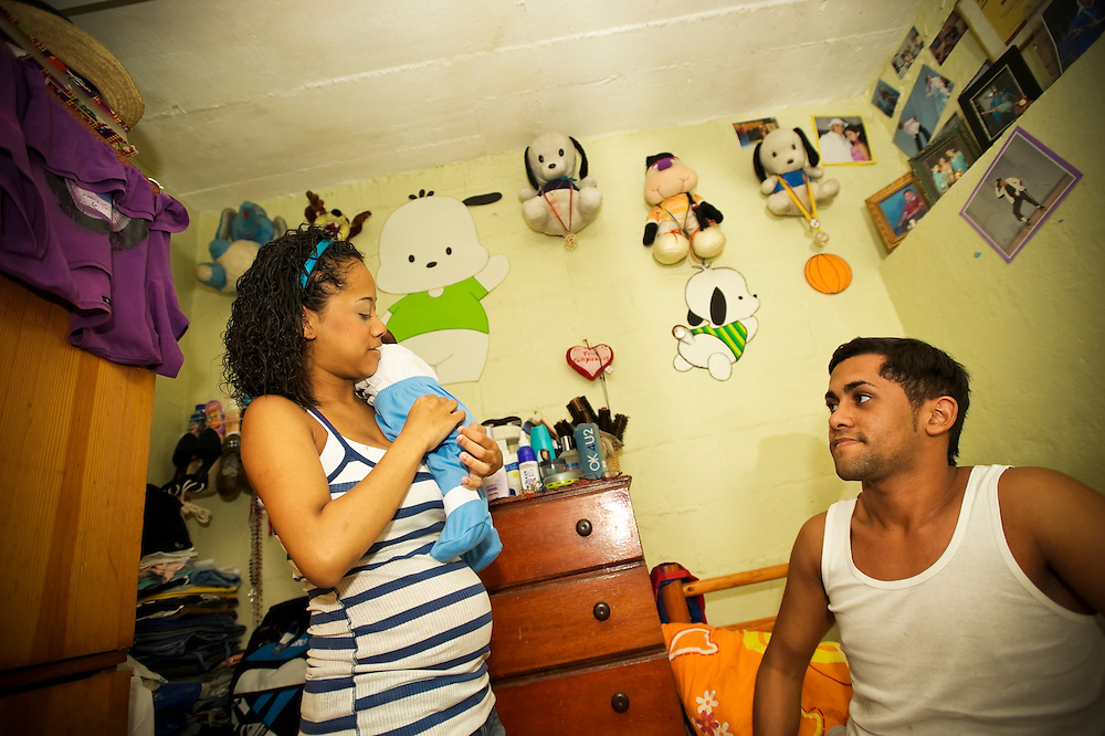 15-year-old mother, Yanaifre Acevedo burps her newborn baby, Dilan, in a slum in Caracas, Venezuela with her cousin, Wleiker Salcedo. Salcedo said he never though Acevedo would be a teen mother, he said he thought she was more intelligent.